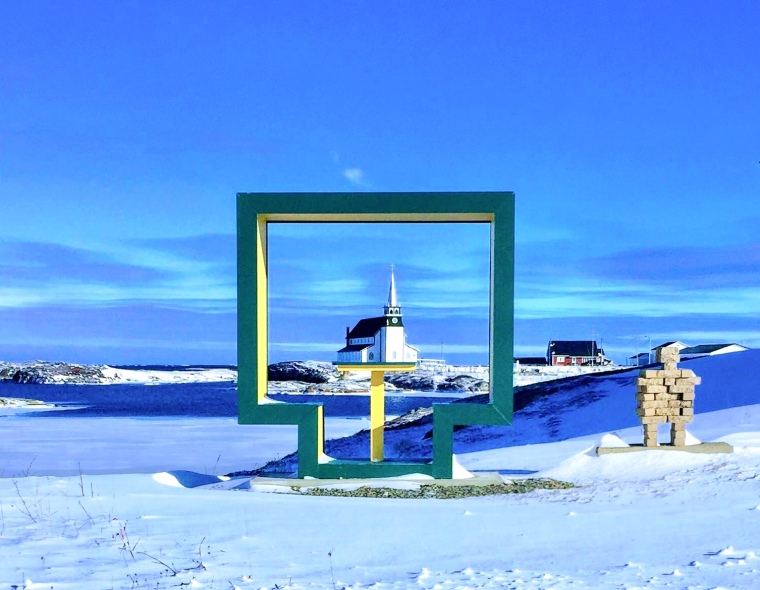 Anglican church in Newtown, Newfoundland framed by an outdoor bench in winter